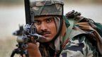 An Indian Army soldier aims his gun during a skirmish with suspected armed rebels at Pindi Khattar village near Jammu