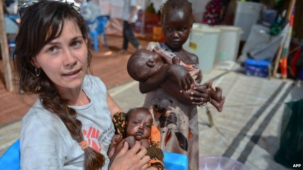 A Medecins Sans Frontieres (MSF) worker holds a South Sudanese baby while two little girls wait for treatment at the MSF hospital in Juba, on 22 February 2014