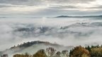A photograph taken from a high perspective, the tops of the hills peeking out over a thick layer of fog.
