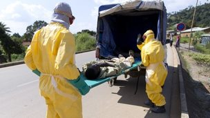 Health workers take a patient to an Ebola treatment centre, Macenta, Guinea