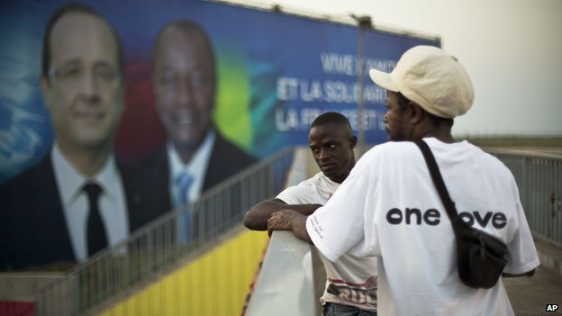 Two Guinean men stand on a pedestrian overpass near the People's Palace where a giant billboard featuring French President Francois Hollande and his Guinean counterpart Alpha Conde is displayed in Conakry, Guinea, 26 November 2014