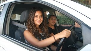 Two smiling Aboriginal women in front seats of white car