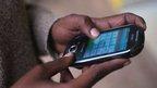 Man in Rwanda using a mobile phone
