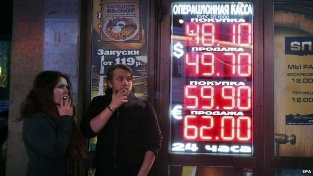 Russians smoke next to electronic boards showing exchange rates