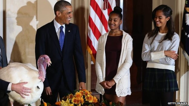 US President Barack Obama smiles at his daughters Sasha and Malia after he pardoned a turkey during a ceremony at the White House on 26 November 2014 in Washington