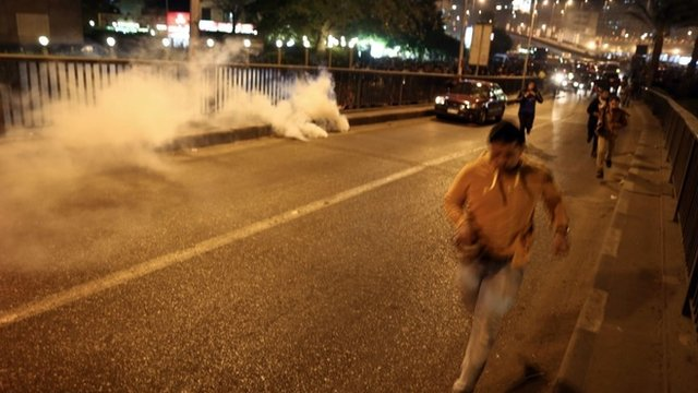 Anti-Mubarak protesters run from smoke grenades