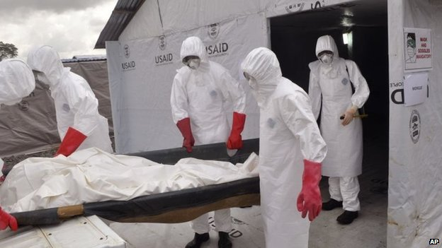 Health workers wearing Ebola protective gear remove the body of a man that they suspect died from the Ebola virus in Liberia