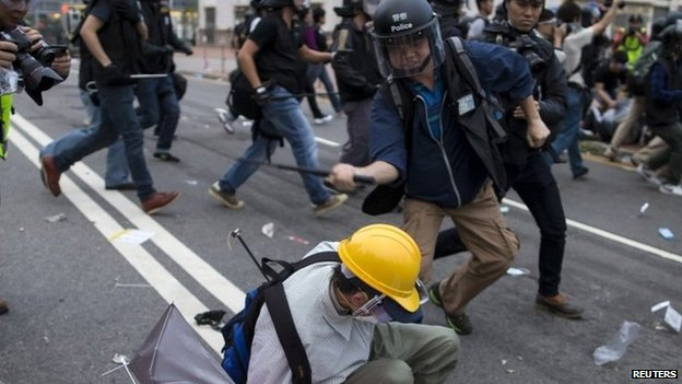 A police officer uses a baton on a pro-democracy protester in Hong Kong. Photo: 1 December 2014