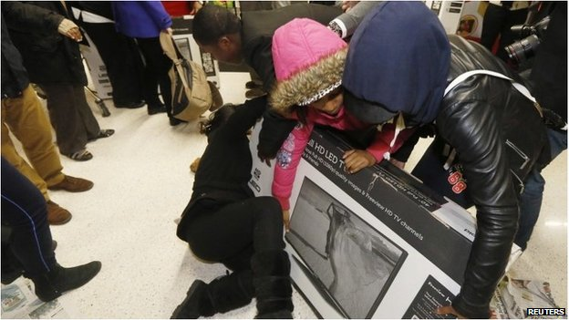 People fighting over a large TV in a box in an Asda store