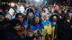 Ukrainians sing the national anthem as they attend a rally marking the first year anniversary of the protests