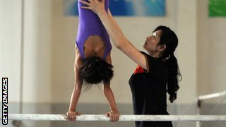 woman coach helping a young gymnast