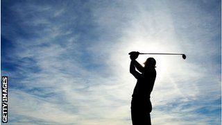 silhouette of man taking a swing with blue sky and clouds in the background