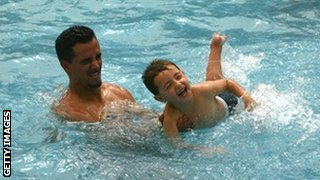 man and his boy in a swimming pool