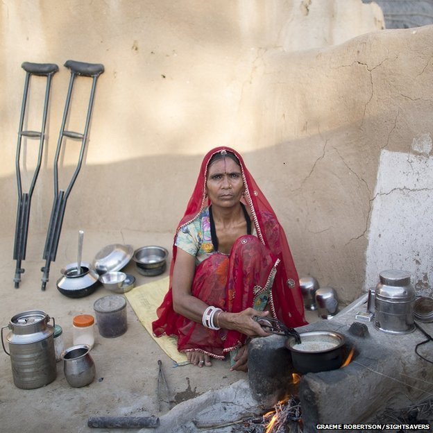 Manju cooking, her crutches are propped up against the wall