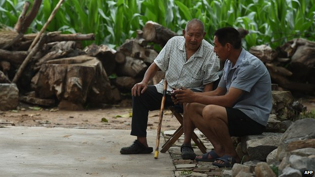 Two men sit near a corn field in Weijian village, in China's Henan province on July 30, 2014.