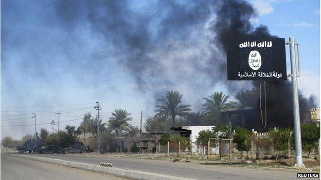 Smoke rises behind an Islamic State flag in Diyala province, Iraq, 24 November 2014