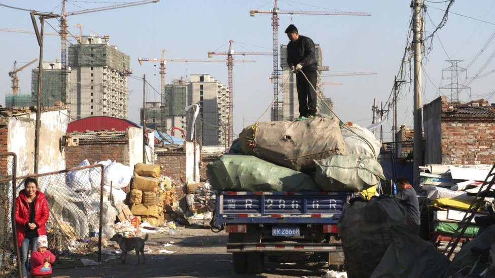 A man stands on top of a truck as he prepares to unload items in Dong Xiao Kou Village