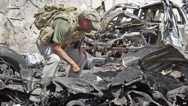 A foreign security officer inspects wreckage at the scene of a car bomb attack that targeted a United Nations convoy, outside the airport in Mogadishu, Somalia on 3 December 2014