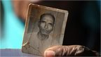 A Bhopal Gas disaster victim holds a frayed photograph of her late husband during a protest rally in Bhopal