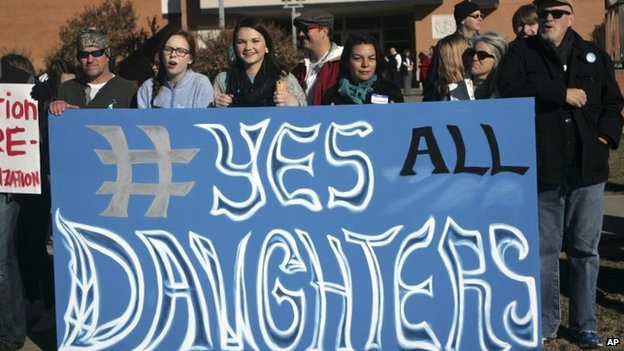 Students and parents holds up a sign during protest outside Norman High School, Monday, Nov. 24, 2014, in Norman, Oklahoma