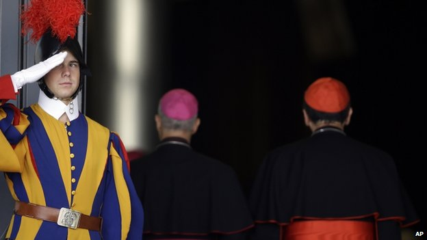 A Swiss Guard salutes two cardinals at the Vatican