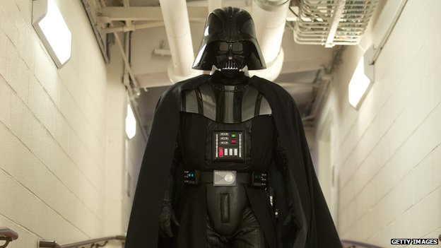 A man in a Darth Vader costume walks down a hallway.