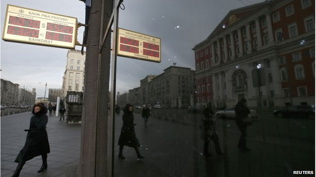 Woman walks past sign showing currency rates in Moscow, 3 December 2014