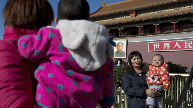In this file photo taken on 16 November, 2013, women cuddle their child at Tiananmen Gate in Beijing, China