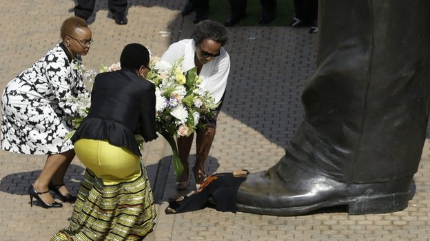 Nelson Mandela's widow Graca Machel, second left, places a wreath to the 9 metre (30 feet) tall bronze statue of the late former South Africa President Nelson Mandela in Pretoria, South Africa,  on 5 December 2014
