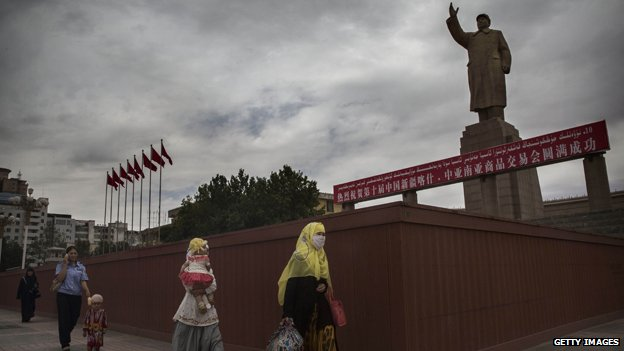 Uighur women walk past a statue of Mao in Kashgar