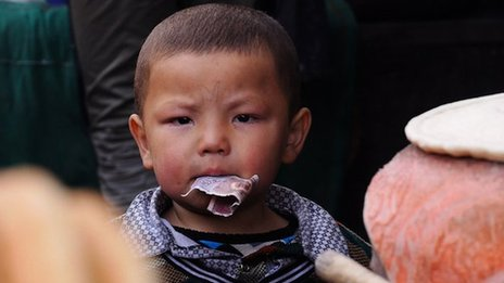 An Uighur child with money in his mouth