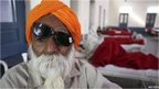 A man sits on a bed while waiting for treatment at a hospital after undergoing cataract removals from a free eye surgery camp, in the northern Indian city of Amritsar December 5