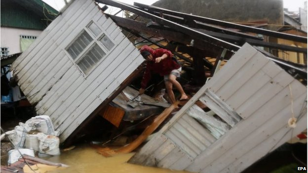 Man climbs over fallen building in  Borongan city, Samar island (7 Dec 2014)