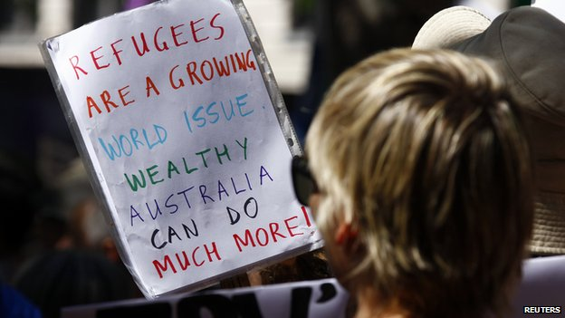 Protesters hold placards at the a rally held in central Sydney on 11 October, 2014