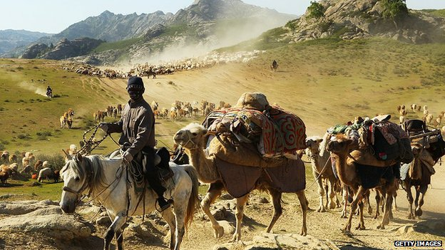 A man on a horse leads a pack of camels in China's far western Xinjiang region