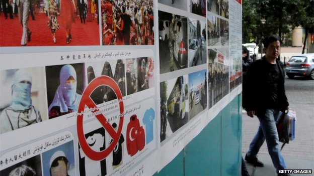 Pedestrians walk past anti-terror propaganda posters pasted along the streets of Urumqi, far west China's Xinjiang region on 16 September, 2014