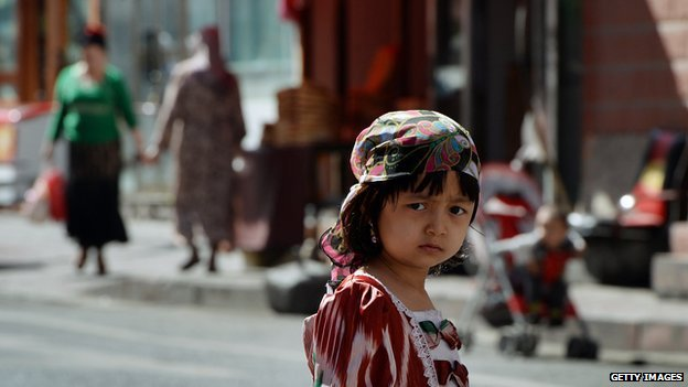 A young Uighur girl waits near the main bazaar in the Muslim quarter of Urumqi, Xinjiang Province on 29 June, 2013