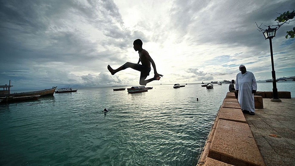 Young man jumping into the sea in Dar es Salam