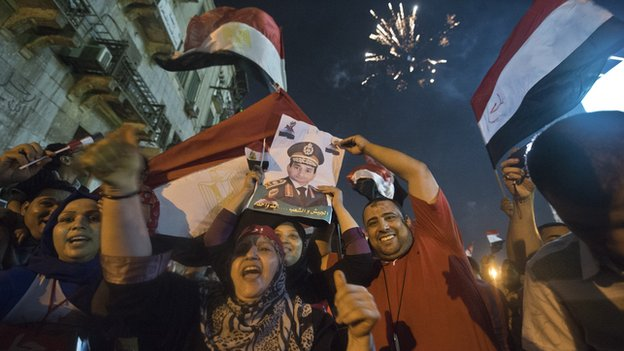People celebrate the ousting of at Tahrir Square with a portrait of Army chief Abdel Fattah al-Sisi after a broadcast confirming that the army will temporarily be taking over from president Mohamed Morsi