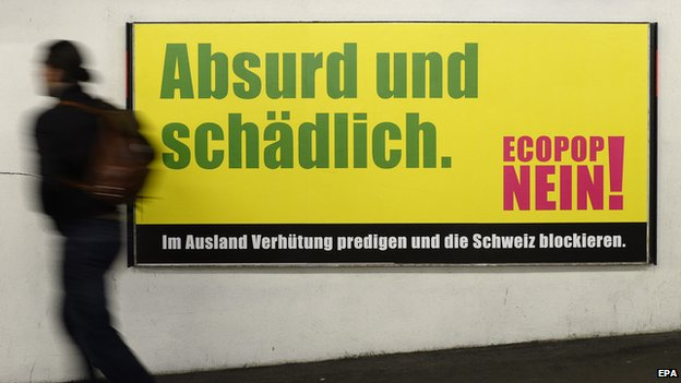 A man passes a poster urging Swiss to vote 'No' to the Ecopop referendum initiative in Zurich, Switzerland, in 2014.
