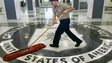 A janitor sweeps over the seal of the Central Intelligence Agency.