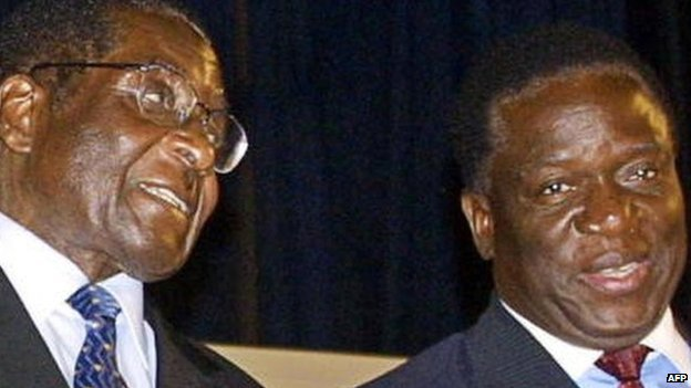 Zimbabwe's President Robert Mugabe (L) talks to Emmerson Mnangagwa on 3 December 2004