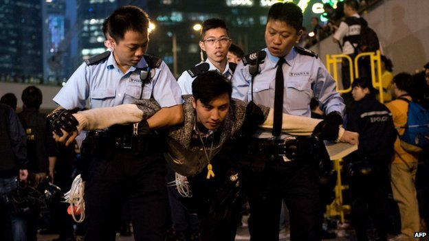 A pro-democracy protester (C) is arrested after police cleared a major pro-democracy protest camp next to the central government offices in the Admiralty district in Hong Kong on 11 December 2014.