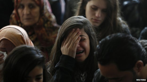 A relative (C) of Palestinian minister Ziad Abu Ein mourns during his funeral in the West Bank city of Ramallah 11 December  2014.