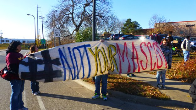 Activists fly a #notyourmascot banner at an anti-Redskins rally