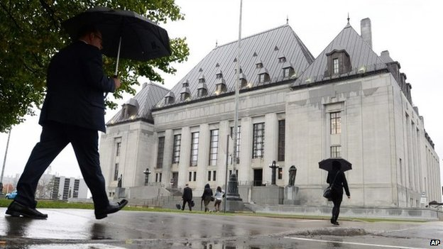 People walk outside the Supreme Court of Canada 15 October 2014 in Ottawa, Ontario.