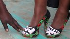 A supporter of the ruling Zanu-PF shows off shoes with her party's colours during elective congress in Harare, 6 December 2014