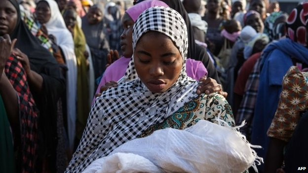Women queue to receive humanitarian aid goods distributed by the Red Cross on 3 December 2014 in the Nigerian city of Yola after fleeing Boko Haram attacks