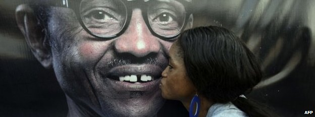 A party member kisses a poster depicting former Nigerian military ruler and presidential aspirant of the opposition All Progressives Congress (APC) Muhammadu Buhari - December 2014