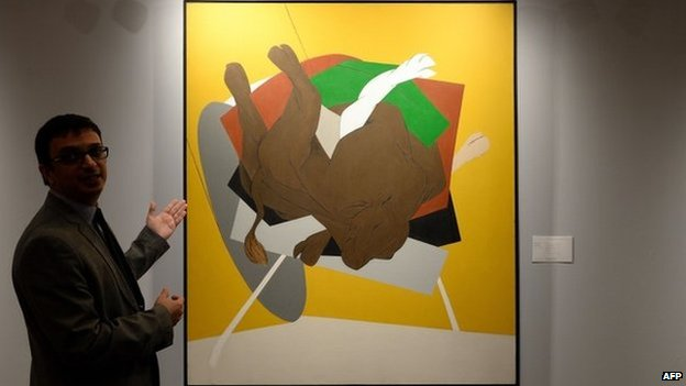 "Nishad Avari, Associate Specialist in South Asian Art, explains Tyeb Mehta""s ""Untitled (Falling Bull)"" during a media preview ahead of Christie""s second auction in India, in Mumbai on December 9, 2014."